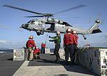Sailors load ammunition onto an MH-60S Sea Hawk helicopter on the flight deck of USS Nimitz. (33090722295).jpg