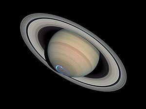 Colour photo of Saturn with overlaid false-colour image of ultraviolet polar aurora