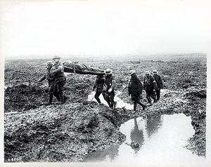 167th (1st London) Brigade - Troops during the Battle of Passchendaele carry a wounded man to the aid post. The terrain pictured and the battle examplified much of the fighting of the Great War.