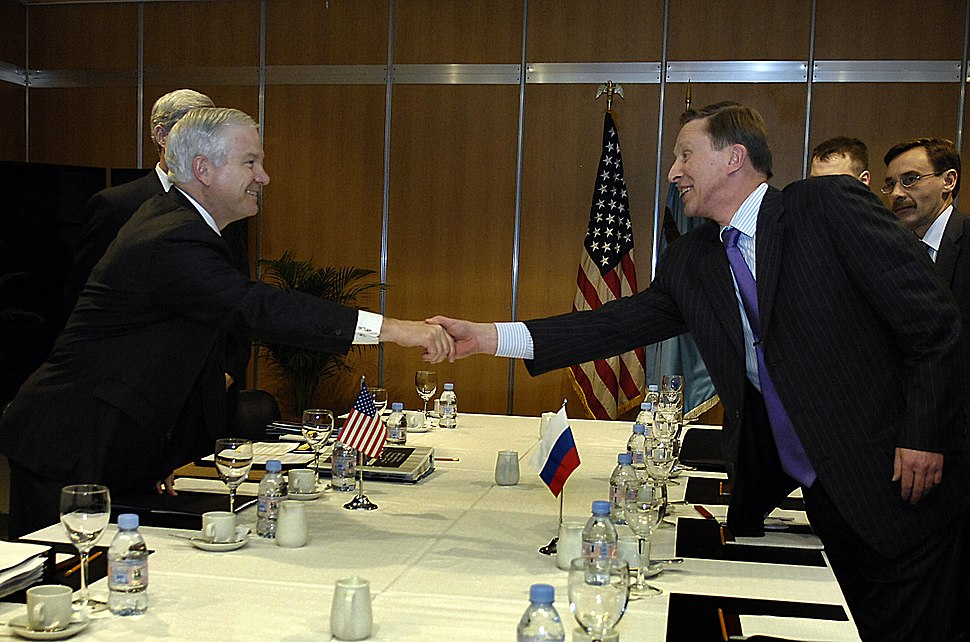 Secretary of Defense Robert Gates and Russian Minister of Defense Sergey Ivanov reach across the conference table