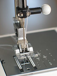 Needle plate, foot and transporter of a sewing machine