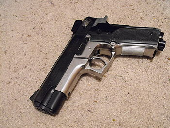 English: a silver bb pistol on an off white carpet