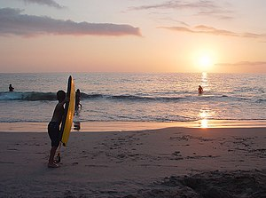 Hapuna Beach State Recreation Area - A young skimboarder prepares to run into the waves at sunset at Hapuna Beach
