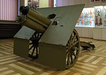a colour photograph of an artillery piece in a museum building