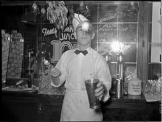 "Milkshake - A soda jerk throws a scoop of ice cream into a steel mixing cup while making a milkshake. On the counter behind him another mixing cup, shake mixers, and a pot of ""Borden's Malted Milk"" powder are visible."