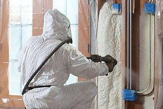 Spray foam - Open cell spray polyurethane foam insulation being applied in wall cavities.