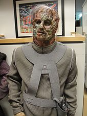 A mannequin wearing a face mask that resembles decomposing flesh and a grey body suit.