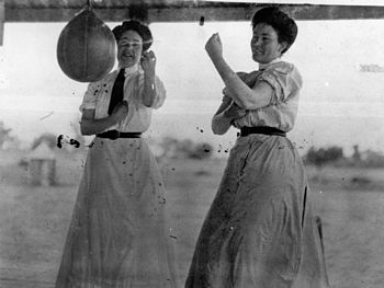 English: Two women sparring with a speed bag B...