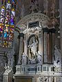 Statue of St John the Good and stained glass window inside Duomo, Milan.jpg