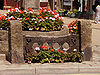 Stocks, made from central dark wooden stock beams with two holes in. The beams are supported by stone pillars. They have flowers planted in front of them, and the market cross, also with flowers, sits behind.
