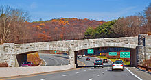 A stone bridge over a divided highway in an autumn landscape