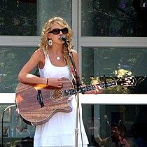 En blond kvinne, kledd av en hvit sundress og store solbriller, i en semi-høyre profilvisning som spiller en akustisk gitar i tre.  Bak henne vises et vindu i dagslys.