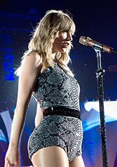 Swift wearing a black and gray patterned body suit standing in front of a microphone singing