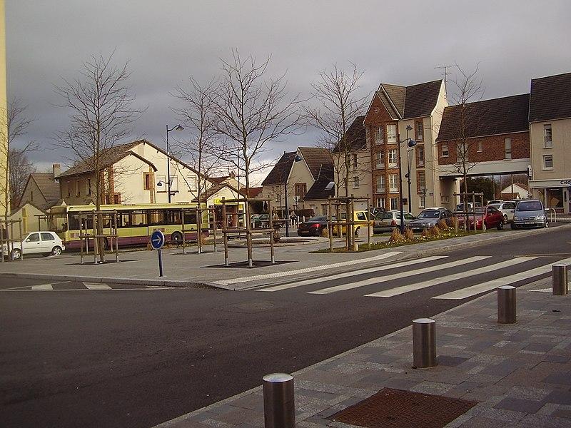 Place du Commerce à Tinqueux avec sa fontaine centrale, sa Poste, sa desserte par bus de la communauté de Reims Métropole. En étant à cheval sur la rue du 29 août 1944, elle fait suite à la place du marché.