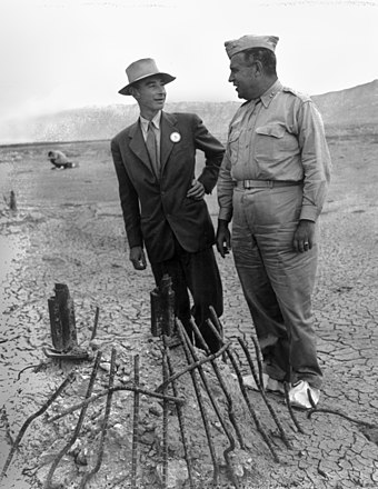 Oppenheimer and Groves at the remains of the Trinity test in September 1945, two months after the test blast and just after the end of World War II. The white overshoes prevented fallout from sticking to the soles of their shoes. Trinity Test - Oppenheimer and Groves at Ground Zero 002.jpg