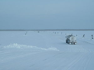 Ice road - Vehicles crossing the Albany River on the winter road running from Moosonee to Attawapiskat in Northern Ontario, Canada. Edge of road is marked by small trees. Heavy vehicles must maintain wide spacing and low speeds.