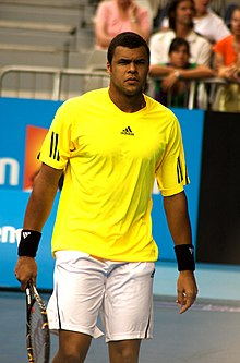 Tsonga in a yellow shirt looking into the camera.