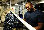 U.S. Navy Ship's Serviceman Seaman Emmanuel Urumeke sorts officer uniforms in the ships laundry department aboard the amphibious dock landing ship USS Tortuga (LSD 46) Aug. 28, 2012, in the Pacific Ocean 120828-N-XZ031-026.jpg
