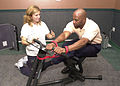 US Navy 040617-N-8861F-001 Italy's Fitness Coordinator, Jamie Kenworthy, from Deleuth, Minn., assists Rodney Contrell, a civilian contractor from Washington, D.C., as he examines exercise equipment on display at a Men's Health.jpg