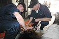 US Navy 050913-N-8502J-002 Electrican's Mate 2nd Class Robert Pedersen and Electrican's Mate 3rd Class Bryan Davis assigned to the amphibious assault ship USS Iwo Jima (LHD 7) replace fuses to an electrical submersible pump.jpg