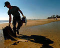 US Navy 051025-N-3729H-065 Electricians Mate 2nd Class Audie Martin, assigned to the Nimitz-class aircraft carrier USS John C. Stennis (CVN 74), gathers debris on a beach in Waveland, Miss.jpg