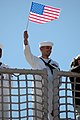 US Navy 060504-N-5055G-024 A Sailor stationed aboard the amphibious dock landing ship USS Carter Hall (LSD 50) waves a flag to his family.jpg