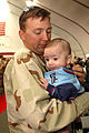 US Navy 070417-N-2456S-062 Storekeeper 3rd Class Kyle Harding, assigned to Navy Customs Battalion (NCB) Romeo, holds his three-month-old son for the first time after NCB Romeo's homecoming.jpg