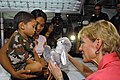 US Navy 070628-N-4954I-021 U.S. Ambassador to the Philippines, The Honorable Kristie A. Kenney, presents a stuffed bunny to a Filipino child as his mother holds him.jpg