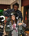 US Navy 091209-N-6999T-001 Parachute Rigger 3rd Class Donte Nickerson helps a little girl try on a survival vest.jpg