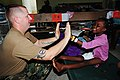 US Navy 100228-N-9643W-026 A Sailor assigned to Naval Beach Group (NBG) 2 plays with a Haitian girl at the New Life Children's Home in Port-au-Prince, Haiti.jpg