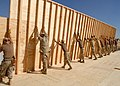 US Navy 100301-N-4440L-196 Seabees assigned to Naval Mobile Construction Battalion (NMCB) 74 and NMCB-4 raise a 12-foot wall section for a southwest Asia hut.jpg