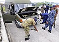 US Navy 100819-N-9643W-414 enior Chief Master-at-Arms Charles Mobley instructs members of the Barbados Defense Force during a vehicle search drill during a Navy Criminal Investigative Service subject matter exchange for Souther.jpg