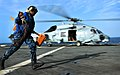 US Navy 100923-N-7948R-443 Boatswain's Mate Seaman Allison Mulligan hurries across the flight deck after removing the chocks from an MH-60S Sea Haw.jpg