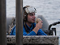 US Navy 110408-N-6505H-201 Aviation Boatswain's Mate (Handling) Airman Christopher Browne talks on a sound-powered telephone to lower Aircraft Elev.jpg