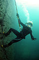 US Navy 110629-N-XD935-163 Navy Diver 3rd Class Bryan Myers climbs to the surface along the pier wall after conducting diving operations.jpg