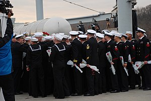 US Navy 111214-N-AW342-102 Sailors assigned to the Los Angeles-class submarine USS Dallas (SSN 700) talk before meeting with loved ones waiting on.jpg