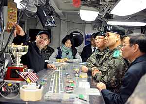 US Navy 120214-N-JO245-025 Lt. Cmdr. Dave Hecht gives distinguished visitors from United Nations Command a tour of flight deck control aboard the n.jpg