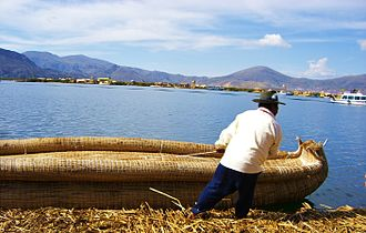 Traditional fishing boat - Uro man pulling a boat made of totora reeds