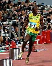 Usain Bolt in a yellow running vest and green shorts just completing a race