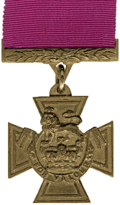"A bronze cross pattée bearing the crown of Saint Edward surmounted by a lion with the inscription ""FOR VALOUR"". A crimson ribbon is attached."