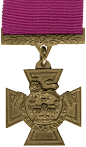 A medal in the shape of a cross hanging from a crimson red ribbon.
