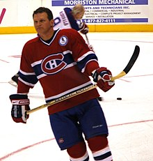 An ice hockey player in his forties stands on the ice wearing a red jersey with horizontal blue and white stripes and his stick held across his waist. He is concentrating on something off in the distance.