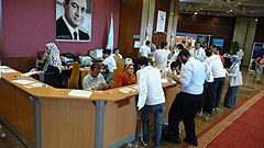 A photograph of a reception desk.  Many of the women seen are wearing headscarves.