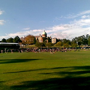 Catholic education in Australia - (L-R) The Memorial Chapel on top of the hill overlooking a game of Australian rules football being played on the Roche Oval, Xavier College, Melbourne