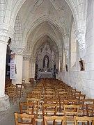Photographie en couleurs de l'intérieur du bas-côté d'une église.