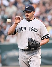 "A man in a gray baseball uniform and navy blue baseball cap catches a baseball with his bare right hand. His jersey reads ""NEW YORK"" across the chest in navy blue letters, while his cap sports a white interlocked ""NY"".His face is heavily stubbled, and he wears a blue baseball glove on his left hand."