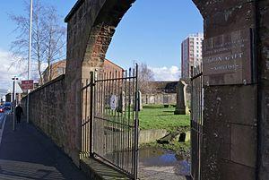 John Galt (novelist) - The old Greenock cemetery entrance from Inverkip Street, with plaque commemorating John Galt, and in the immediate background John Galt House.