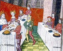 Dans une salle au carrelage bicolore vert et dont les murs percés de fenêtres en ogives sont partiellement masqués d'une longue tapisserie rouge, deux tables sont dressées; à celle de droite, sont assis côte à côte deux seigneurs derrière lesquels se tient une femme debout; à celle de gauche, en vis-à-vis, un seigneur couronné et sa dame regardent un serviteur qui va trancher un haut pâté. Trois autres personnages, dont un bouffon, complètent la scène.