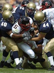 Quando um jogador leva um tackle e cai no chão é marcado um down.