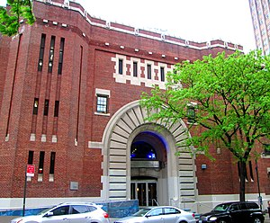 A brick building with a big central arched entrance